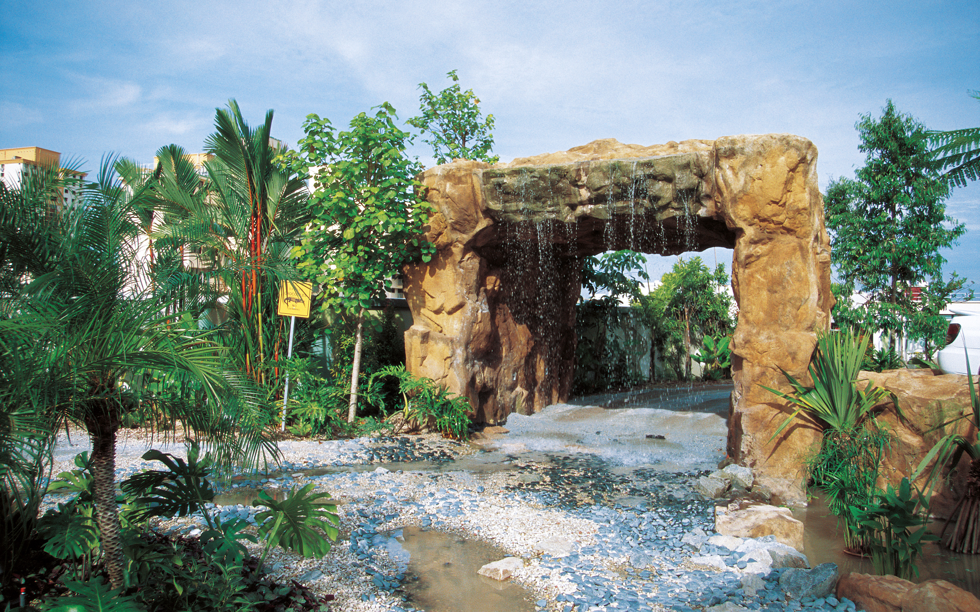 Archway with waterfall and tropical vegetation