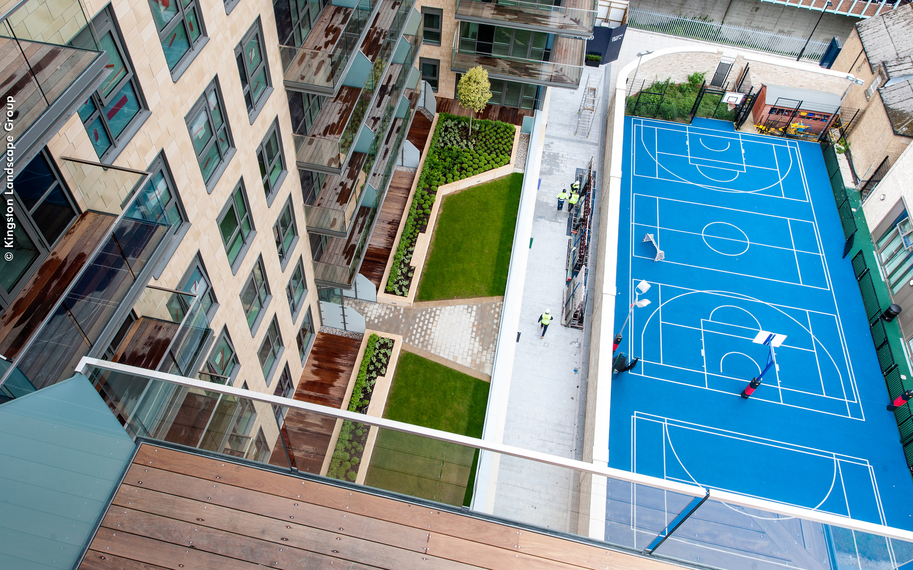 Bird's eye view into a green courtyard and a basketball court