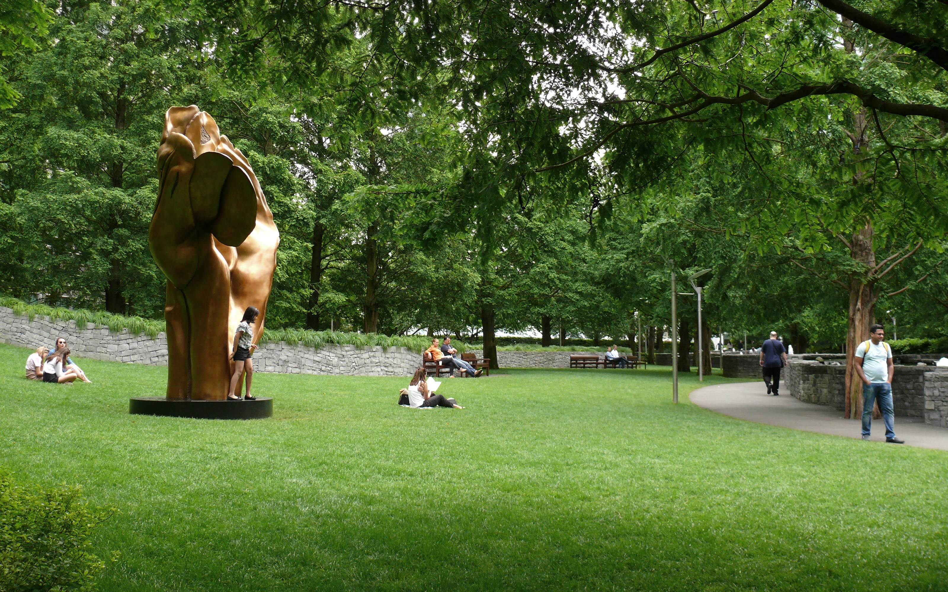Bronze sculpture on the lawn and people relaxing in the park