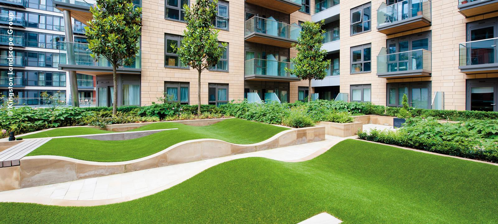 Undulating lawn patch surrounded by condominiums