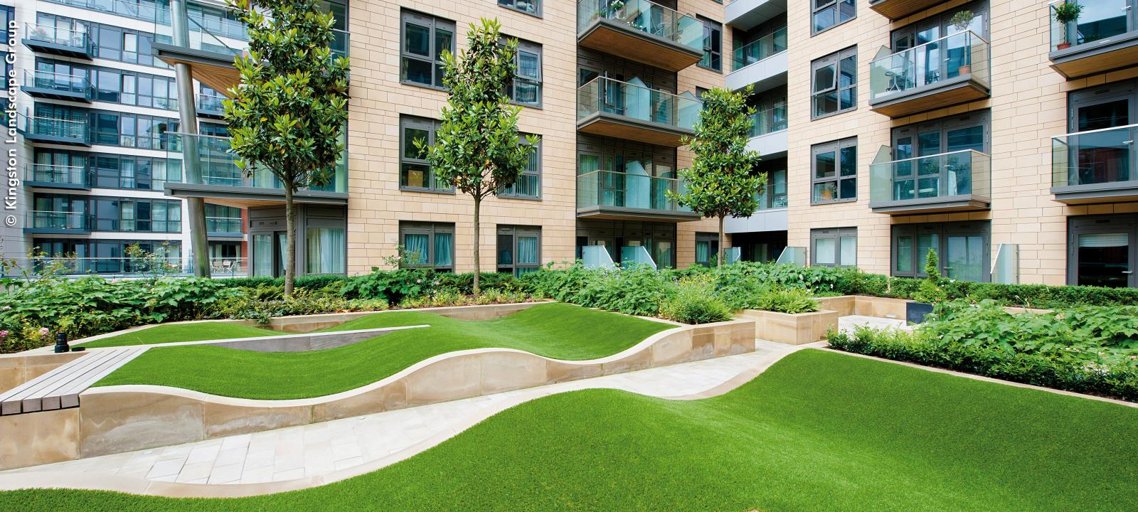 Courtyard with rolling mounds made from grass surrounded by residential blocks