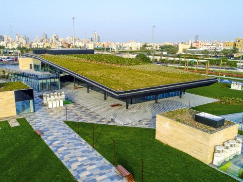 Building with a green roof and surrounded by lawn in a big city