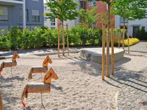 Playground with little wooden horses and trees