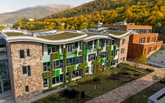 Building with natural stone façade, vertical greening and wavelike green roofs