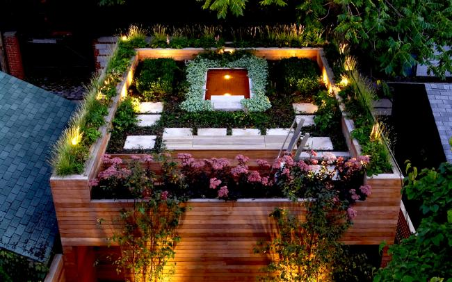 Illuminated roof garden with a pond at night